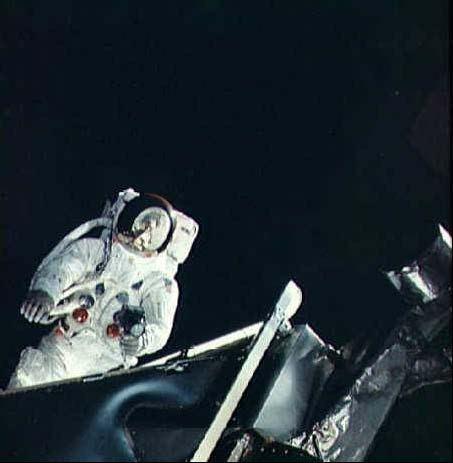 """Rusty Schweickart na """"terase"""" LM Spider počas EVA. Na chrbte má """"ruksak"""" s PLSS a v jeho slnečnom filtri sa odráža CM Gumdrop."""