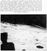 """Přistávací oblast si kosmonauti prohlédli již na oběžné dráze kolem Měsíce, kde byl LM ještě spojen s CSM. V okamžiku pořízení tohoto snímku severozápadní části Moře klidu z okénka LM, obíhali na dráze ve výši 110 km. Vlevo dole zakrývá část výhledu čtveřice manévrovacích trysek. Velký kráter vpravo dole je Maskelyne, nad ním Maskelyne B. Skupinu pahorků uprostřed obrázku, vlevo od Maskelyne, nazývají kosmonauti Boot Hill, podobnou kousek nad ní Duke Island. Menší kráter mezi Duke l. a Maskelyne B přejmenovali na """"Umývadlo"""" /Wash Basin). Přistávací oblast se nachází na rozhraní světla a stínu vpravo od kráteru Moltke. Vlevo od něj je vidět rýha Hypatia (dálnice U.S.1), zakončená pohořím Thud Ridge. Těsně u levého okraje obrázku je kráter Torricelli C"""