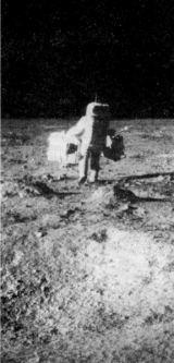 Edwin Aldrin obtížený pasivním seismometrem (vlevo) a laserovým odrážečem (vpravo) odchází instalovat oba přístroje