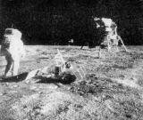 """Jedna z mnoha fotografií, které za měsíční procházky pořídil Neil Armstrong, ukazuje """"základnu Tranquillity"""". Vpředu uprostřed je instalován pasivní seismometr (Passive Seismic experiment Package), poněkud za ním laserový odrážeč (Laser Kanging Retro-Reflector), úplně vzadu televizní kamera a americká vlajka. Experiment Bernské university je umístěn před měsíční sekcí. Vlevo stojí kosmonaut Edwin Aldrin"""