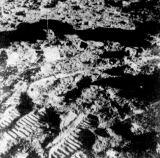 Mezi šlépějemi a otisky kol vozíku stojí gnomon, pomocí kterého určují kosmonauti orientaci vzorků na povrchu