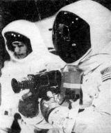 """Neil Armstrong a jeho Hasselblad 500EL Data Kamera s objektivem Carl Zeiss Biogon 60 m/5,6. Všimněte si """"taháku"""", který má Armstrong připevněn na levém předloktí"""