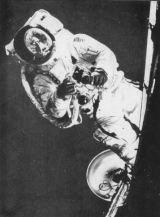 Americký astronaut sfotoaparátem Hasselblad při EVA. Vjeho přilbě se zrcadlí Země.